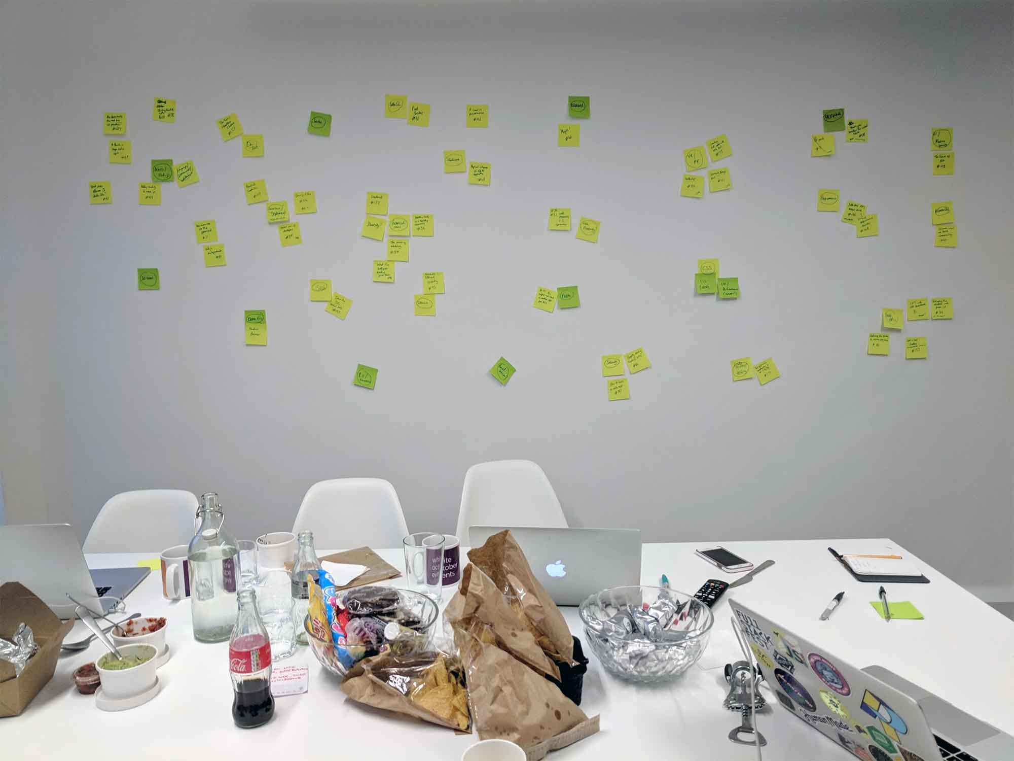 A wall of post-it notes in front of a table holding laptops and snacks